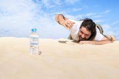 Durstiger Mann in der Wüste erreicht für eine Flasche Wasser Stockfotografie