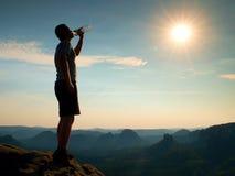 Durstiger Wanderer in den schwarzen Hosen trinkt von der Flasche Wasser Verschwitzter müder Tourist auf der Spitze des felsigen P Lizenzfreie Stockbilder