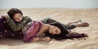 Durstiges Legen der Frauen in eine Wüste Verloren in Wüste durind sandshtorm lizenzfreies stockbild