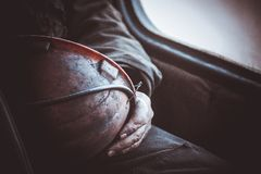 Durty hands of miner worker hold helmet Stock Photos
