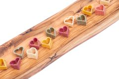 Durum wheat semolina heart-shaped 5 flavors pasta with vegetables arranged on long olive wood plate isolated on white. Background. Valentine`s Day stock image