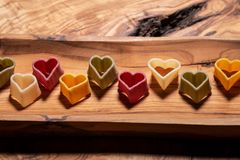 Durum wheat semolina heart-shaped 5 flavors pasta with vegetables arranged on long olive wood plate. Valentine`s Day royalty free stock photo