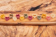 Durum wheat semolina heart-shaped 5 flavors pasta with vegetables arranged on long olive wood plate. Valentine`s Day stock image