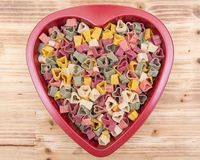 Durum wheat semolina heart-shaped 5 flavors pasta with vegetables in heart shaped container on natural wooden tray. Valentine`s Day stock photos