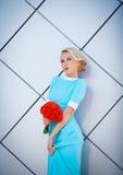 Durvende blonderebel met helder geschilderde lippen In een lange blauwe kleding met boeket van rood ter beschikking Tegen de acht Stock Afbeeldingen