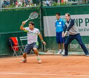 Dusan Lajovic plays second round in Roland Garros 2014. PARIS - MAY 29: Dusan Lajovic of Serbia plays forehand return while the umpire shows that the ball was in Stock Photos