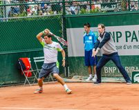 Dusan Lajovic plays second round in Roland Garros 2014. PARIS - MAY 29: Dusan Lajovic of Serbia plays forehand return while the umpire shows that the ball was in Stock Photo