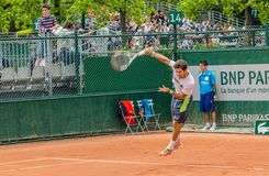 Dusan Lajovic plays second round in Roland Garros 2014. PARIS - MAY 29: Dusan Lajovic of Serbia servs during the 2nd round match at French Open, Roland Garros on Royalty Free Stock Photo