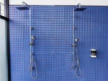 Dusche auf blauer Fliesenwand Stockbild