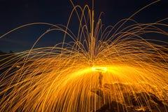 Duschen des heißen Glühens funkt von spinnender Stahlwolle auf dem Felsen Stockfotos