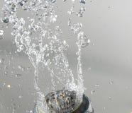Duschkopf mit Wasser auf Grau Stockfotografie