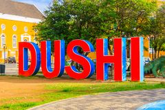 Dushi writting on the ground in Cucacao. Willemstad, Curacao - FEBRUARY 14, 2018: Big letters on the ground spelling DUSHI in Curacao Stock Image