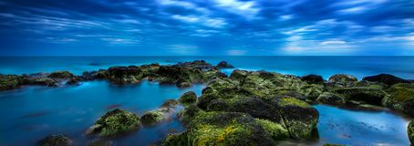 Dusk πέρα από την ήρεμη μπλε θάλασσα πέρα από τον ωκεάνιο και νεφελώδη ουρανό Στοκ Εικόνα