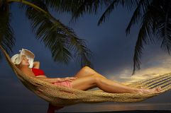 Dusk. View of a woman lounging in hammock during sunset Royalty Free Stock Photo