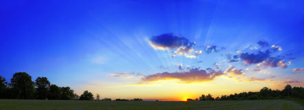 Dusk. Beautiful hi-res panorama of a sunset in the country. Beams of sunlight cutting through the clouds on a late summer evening Royalty Free Stock Photos