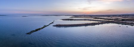 Dusk aerial panoramic seascape view of Olhao salt marsh Inlet. Dusk aerial panoramic seascape view of Olhao salt marsh Inlet, waterfront to Ria Formosa natural Royalty Free Stock Image