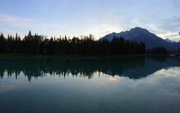 Banff, Bow River, evening reflection with mountain in background Royalty Free Stock Photos