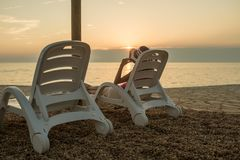 Dusk on a beach at sunset as a woman relaxes on a recliner chair. Dusk on a pebble beach at sunset as a single woman relaxes on a recliner chair facing out over Royalty Free Stock Photos