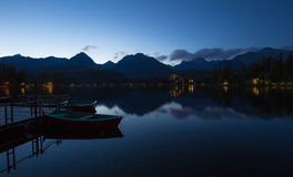 Dusk on a calm plateau of a mountain lake, water - borne peaks and moorings on the shore. View of the Dusk on a calm plateau of a mountain lake, water - borne Stock Images