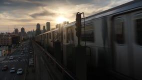 Dusk establishing shot of manhattan skyline with subway car passing by. A dusk establishing shot of the Manhattan skyline as seen from Queens as two elevated stock footage