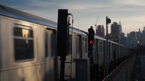 Dusk establishing shot of Manhattan skyline with subway car passing by. A dusk establishing shot of the Manhattan skyline as seen from Queens as two elevated stock video footage