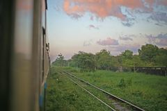 Pink clouds hover over the tracks deep in the countryside of the Burmese Railway, between Yangon and Mandalay. Dusk falls aboard the sleeper train from Yangon to Stock Images