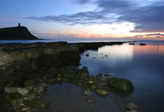 Dusk at Kimmeridge Bay. Long exposure with fill-in flash taken at dusk and featuring a partially-exposed geological ledge and a silhoutted hill and 19c tower in stock photos