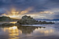 Dusk at the lonely beach. Dusk at the Arrietara beach, in Sopela, Basque Country, Spain. With the rock Peña Txuri dominating the image royalty free stock images