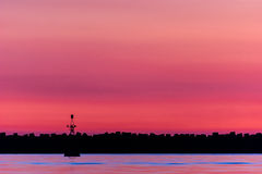 At dusk. Magenta sunset with birds perched on a lighthouse Stock Images