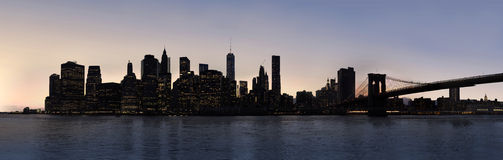Dusk Manhattan panorama. Dusk panorama of New York City Manhattan and Brooklyn Bridge, view from Green point pier Royalty Free Stock Photo