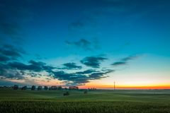 Dusk over field wind turbines in summer Royalty Free Stock Photo