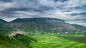 Dusk over green field in mountain at spring, Castelluccio, Italy stock footage