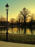 Dusk in the park. Park with calm water pond in the middle. Trees are bare of leaves in this autumn scene and the street lamp in the foreground has yet to be stock image