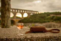 Dusk at Pont du Gard - France. A glass of wine and a purse sit on a limestone wall at dusk.  The ancient Roman aqueduct Pont du Gard can be seen in the Royalty Free Stock Photos