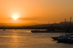 Dusk in the port. Port with silhouettes of the ships during beautiful sunset Stock Photos