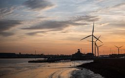 Dusk at the Port of Tilbury, Essex, UK. Dusk sunset view of the Port of Tilbury with the empty ferry terminal on the banks of the River Thames and wind turbines Stock Photo