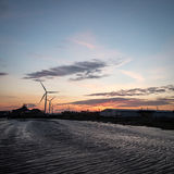 Dusk at the Port of Tilbury, Essex, UK. Dusk sunset view of the Port of Tilbury with the low tide banks of the River Thames and wind turbines turning in the Stock Photo