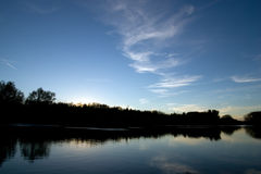 Dusk reflection of tree line on the water Royalty Free Stock Images