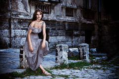 Dusk scene. Young woman in front of old stone house, outdoor portrait at dusk Royalty Free Stock Image