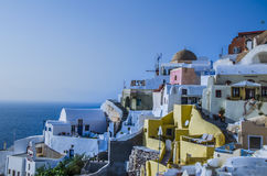 At dusk the sun bathes the traditional and colorful Greek houses Stock Photos