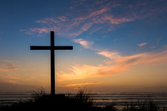 Dusk Sunset Salvation Cross. Black cross on a beach with a dusk sky sunset behind it Royalty Free Stock Photography