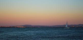 Dusk on the Tagus River. A sailboat sails at dusk on the Tagus River. Lisbon, Portugal Stock Photo
