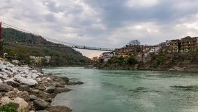 Dusk time lapse at Rishikesh, holy town and travel destination in India. Colorful sky and moving clouds over the Ganges River. Peo. Ple crossing on the stock video footage