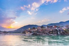 Dusk time at Rishikesh, holy town and travel destination in India. Colorful sky and clouds reflecting over the Ganges River. Stock Image