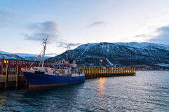 Dusk in Tromso pier with fishing vessel parked Royalty Free Stock Images