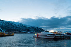 Dusk in Tromso pier with yachts and cruise ships Royalty Free Stock Image