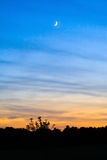 Dusk into Twilight. Beautiful shot in Virginia of the sun going down creating dusk and leading into twilight with the moon shining above Royalty Free Stock Image