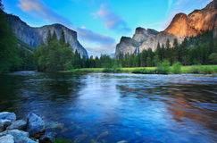 Dusk at Yosemite. El Capitan and the Cathedral Rocks (with Bridalviel Falls) seen from the Merced River at dusk Royalty Free Stock Photo