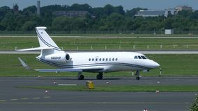 Dassault Falcon 2000EX taxiing at the Dusseldorf airport. Dusseldorf, Germany - July 22, 2017: side view of white business jet Dassault Falcon 2000EX N669HP stock video footage