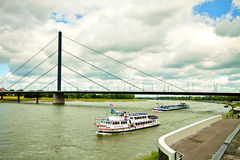 Dusseldorf, panoramic view of Rhine  river with maritime traffic. Dusseldorf, view of Rhine river from waterfront with touristic boat, ewer and bridge Stock Photography